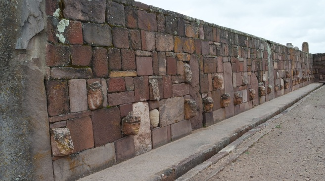 "Wall of the Temple of Kalasasaya (""Place of the Vertical Stones""). It is built like a stockade with 12 foot high columns jutting upward at intervals, each of these being carved into human figures."